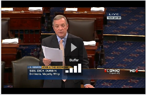 Senator Durbin, a grey haired gentelman in a suit, reads off a sheet of paper from a poduium surrounded by other chairs.