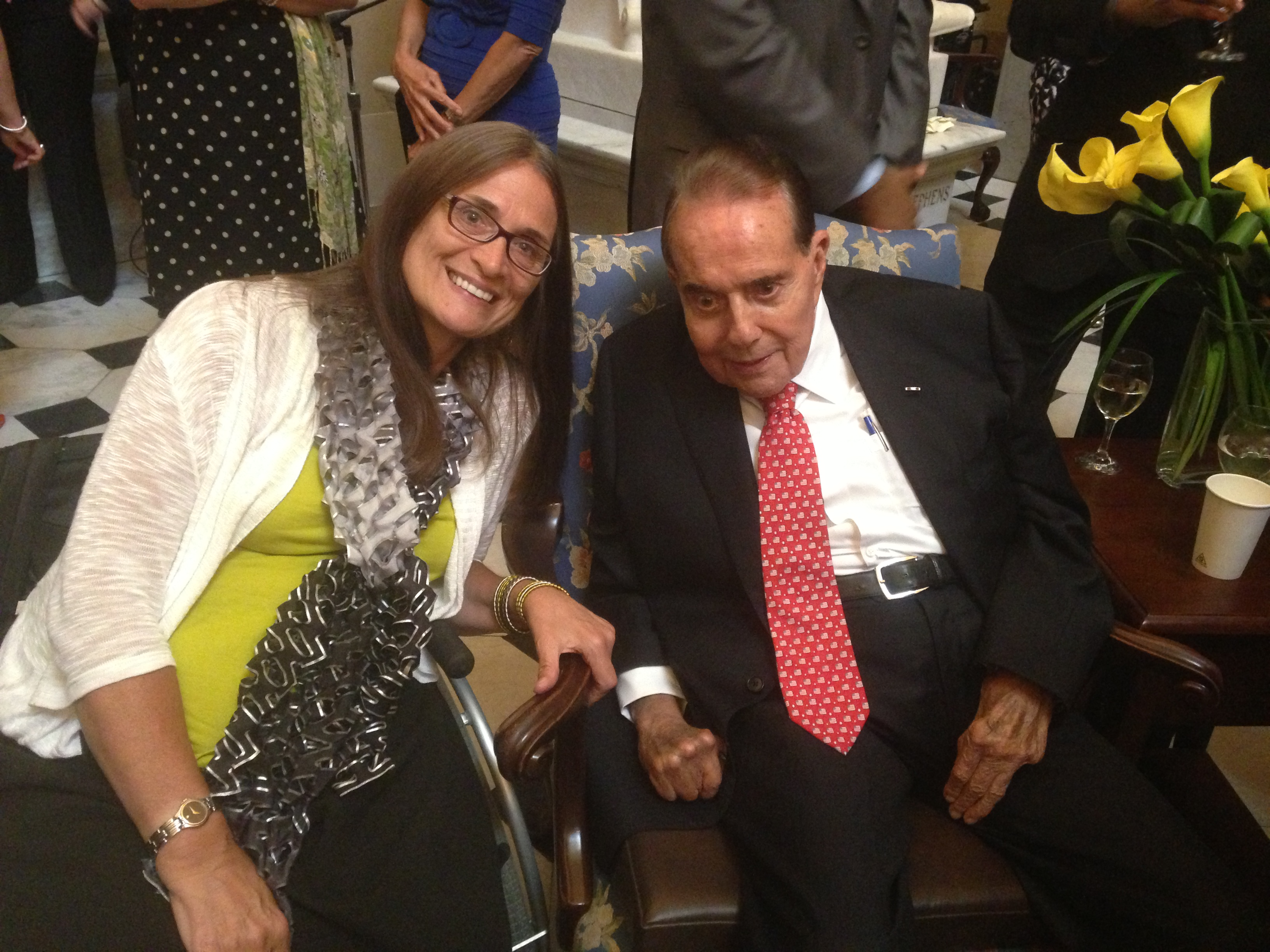 A woman and a man in a suit, both in wheelchairs, lean in and smile at the camera