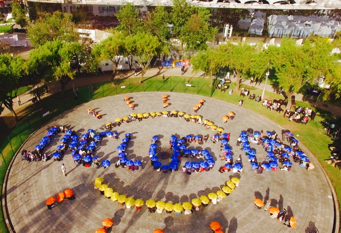 "People holding blue umbrellas form the word ""Inclusion"" when viewed from directly above. People holding yellow and orange umbrella form the sun."
