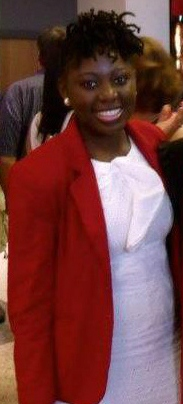 A smiling African American woman smiles at the camera wearing a white top with a red jacket.