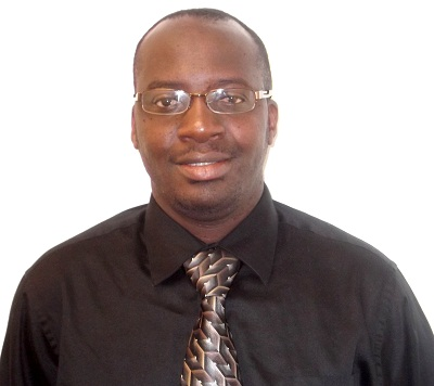 An African Gentleman wearing a black shirt and light tie and glasses.