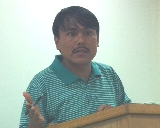 A man of Nepalese decent speaks at a lectern wearing a green and white striped shirt.