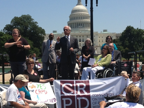 A white haired gentleman (former Representative Tony Coehlo) stands in front of the US Capitol speaking into a mic surrounded by disability advocates and an ASL interpreter