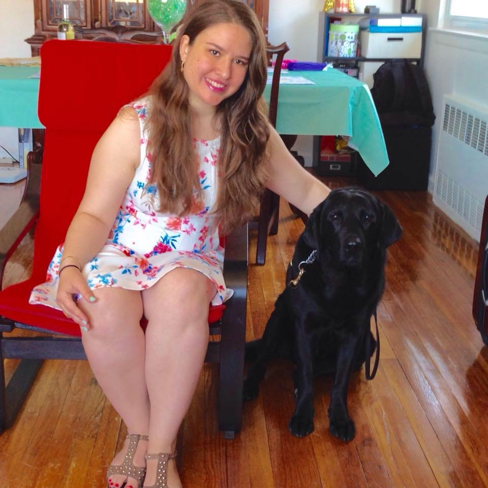 Woman with long brown hair with a black lab service dog