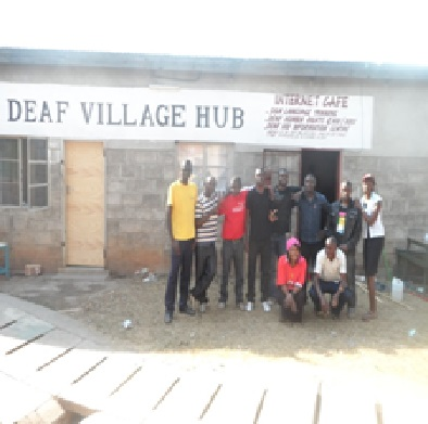 a group of yound men stand in front of a cinderblock building under a sign that says Deaf Village Hub
