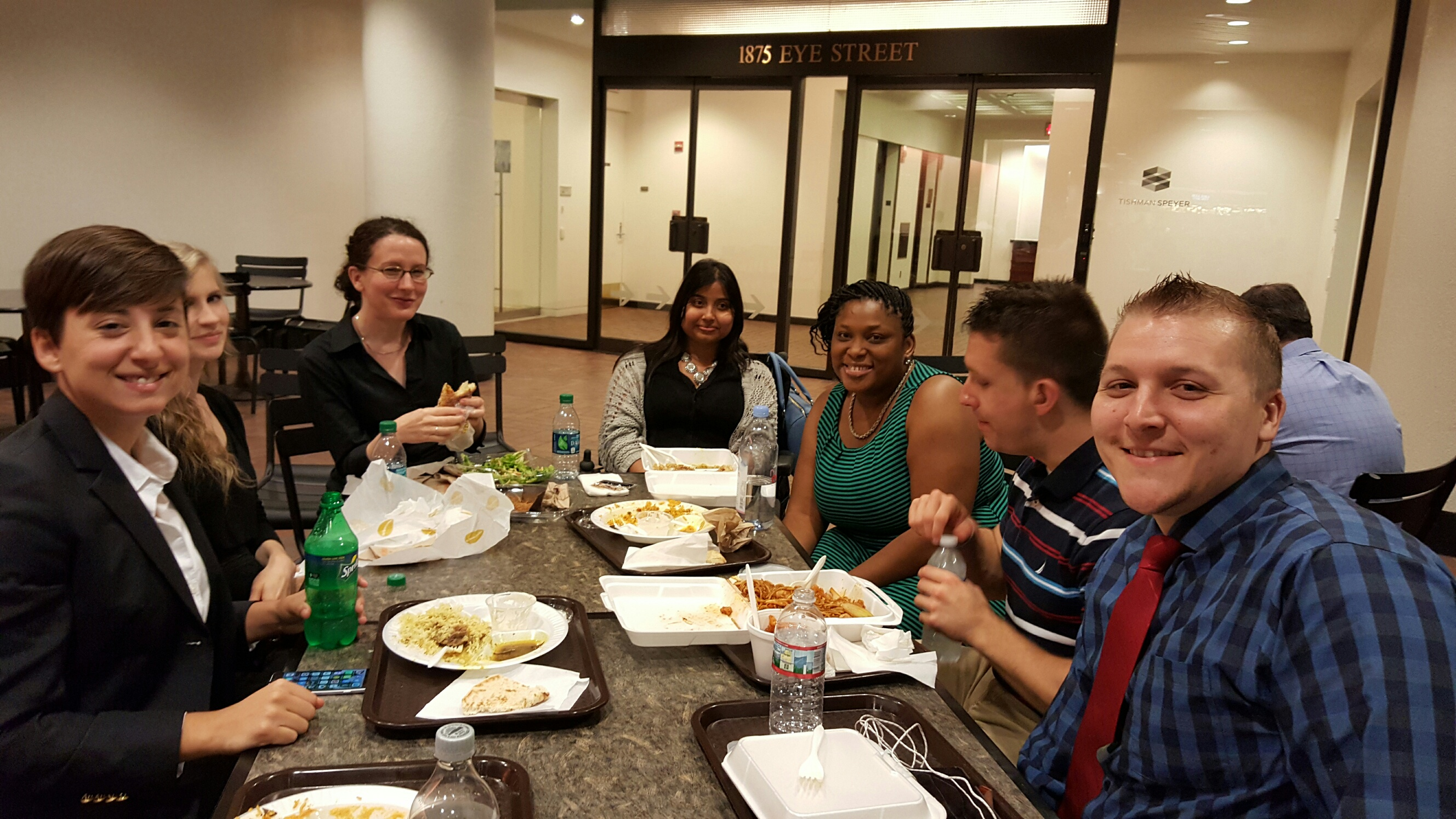 A group of USICD program interns, with sign language interpreters, eat lunch at a cafeteria during training and orientation week