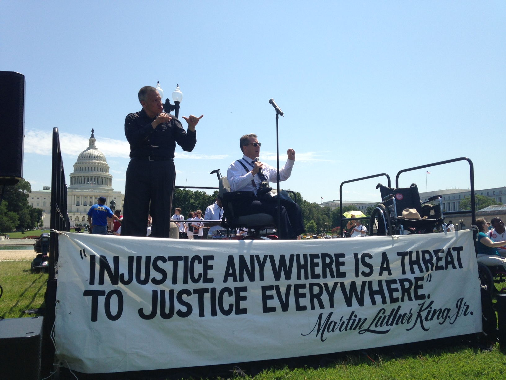 On an open air stage, a man in a wheelchair speaks into a mic with his fist raised while a man interprets in ASL beside him